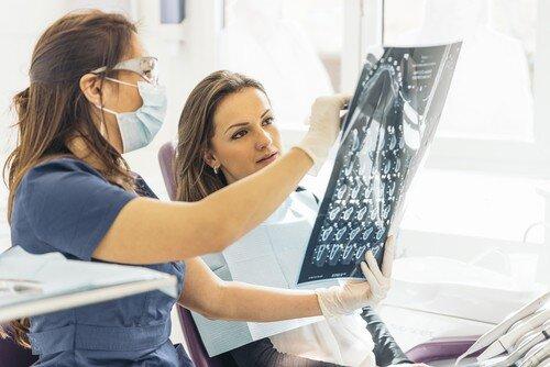 woman and dentist examine x-ray